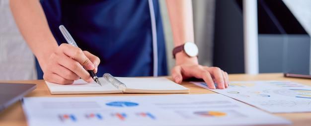 Taccuino di scrittura della donna di affari e lavorare alla tavola e ai documenti finanziari in ufficio.
