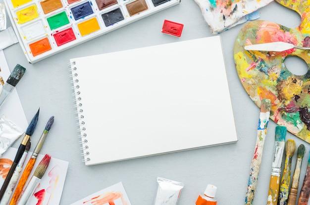 Taccuino di vista superiore circondato da elementi di pittura