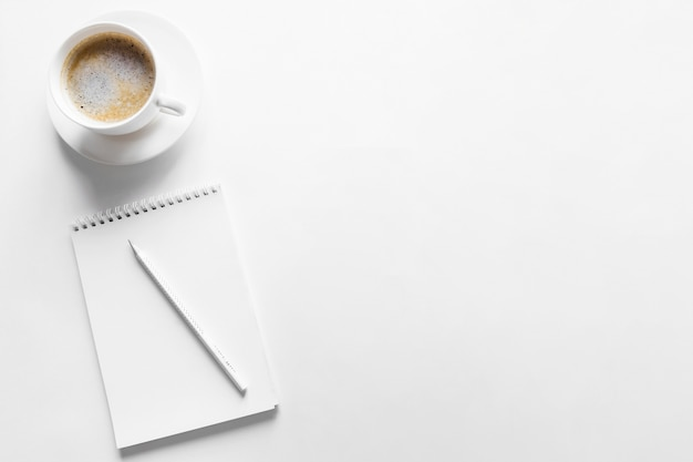Taccuino e caffè di vista superiore su fondo bianco