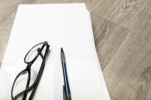 Taccuino e matita in bianco con i vetri sulla tavola di legno