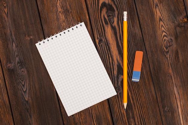 Taccuino e matita in bianco su una superficie di legno