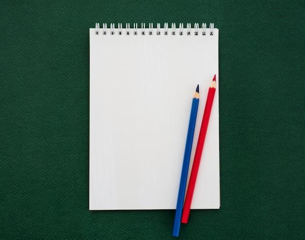 Taccuino e matite colorate su priorità bassa verde