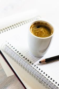 Taccuino e nota di scrittura con una tazza di caffè