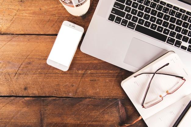 Taccuino e occhiali vicino a laptop e smartphone