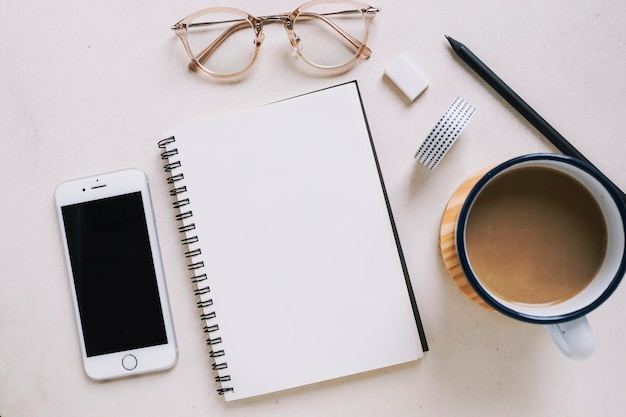 Taccuino e occhiali vicino a smartphone e caffè