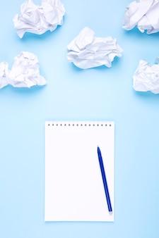 Taccuino e penna bianchi su fondo blu intorno a carta sgualcita sotto forma di nuvole. concetto di redazione di lista dei desideri e sogni