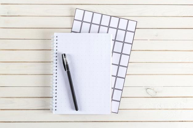 Taccuino e penna di vista superiore sullo scrittorio di legno bianco