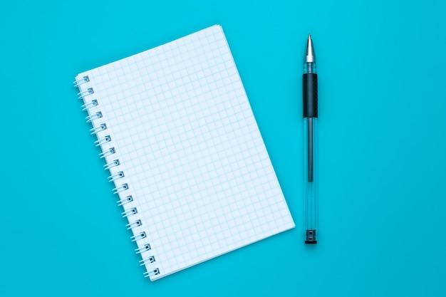 Taccuino e penna in bianco su fondo blu. copia spazio. concetto di educazione.