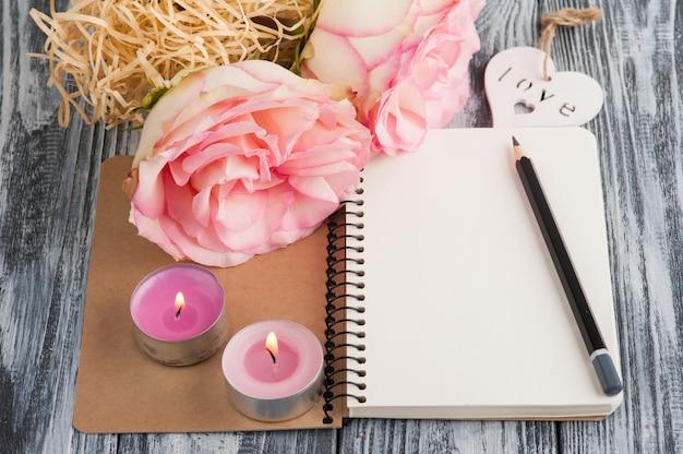 Taccuino, fiori e candele accese