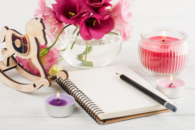 Taccuino in bianco, candele, fiori di eustoma