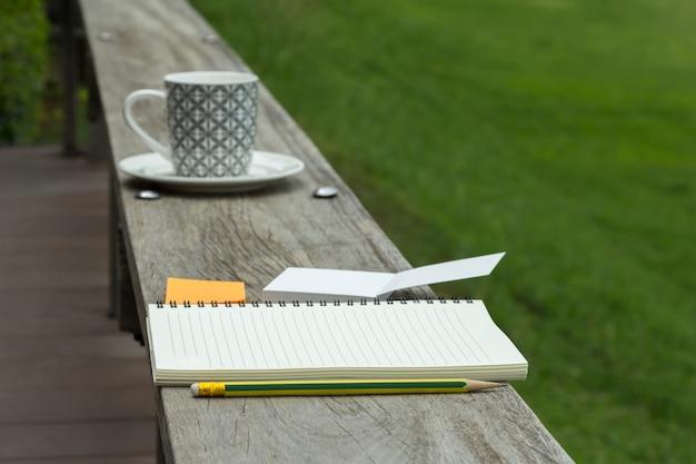 Taccuino in bianco con blocco note e matita su legno
