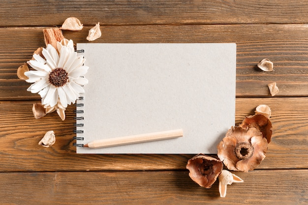 Taccuino in bianco con il fiore sulla tavola di legno d'annata