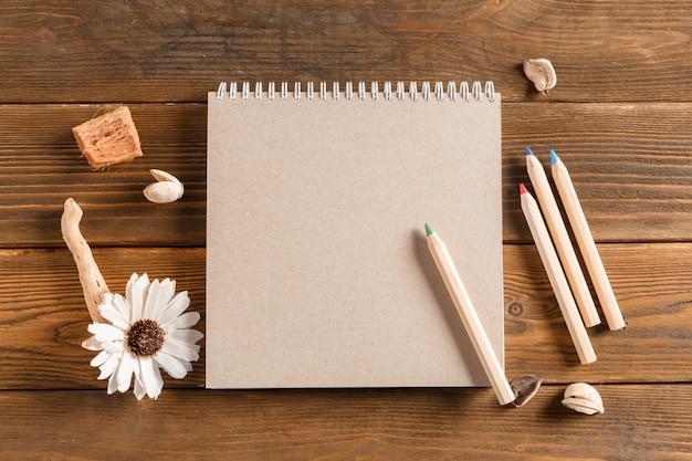 Taccuino in bianco con il fiore sulla tavola di legno dell'annata