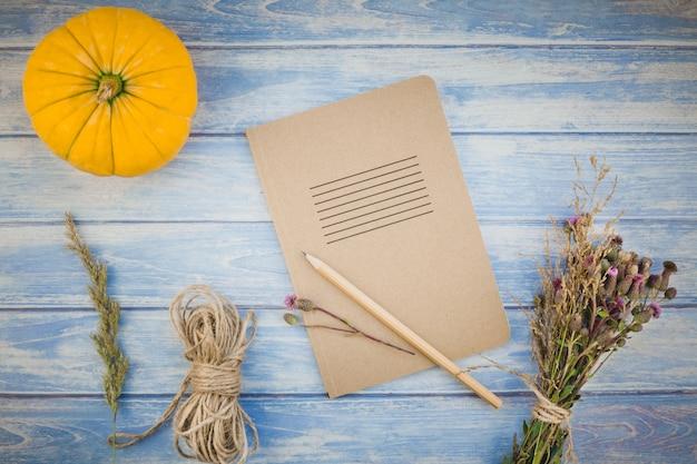 Taccuino in bianco con la matita e le zucche di autunno