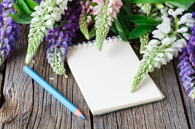 Taccuino in bianco con la penna e mazzo della tavola di legno dei fiori. concetto di scrittura del diario