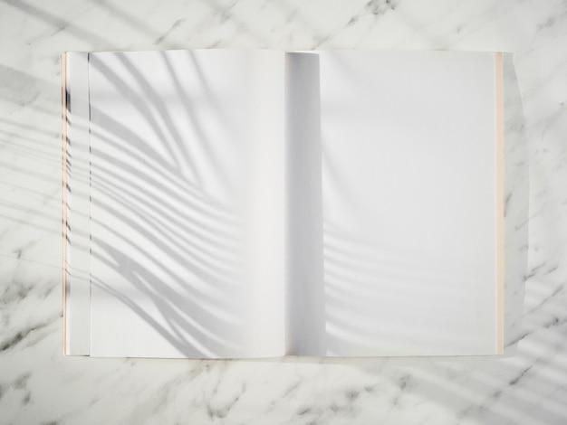 Taccuino in bianco con la vista superiore delle ombre