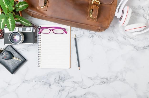 Taccuino in bianco merita borsa in pelle vintage e fotocamera vintage sul tavolo di marmo
