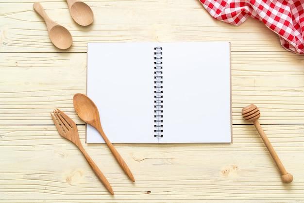 Taccuino in bianco per la nota del testo su superficie di legno con copia sapce