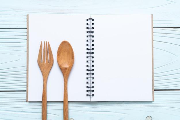 Taccuino in bianco per la nota di testo su superficie di legno con copia sapce