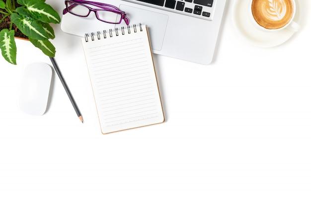 Taccuino in bianco su laptop e occhiali con caffè caldo isolato su sfondo bianco, vista dall'alto e spazio di copia