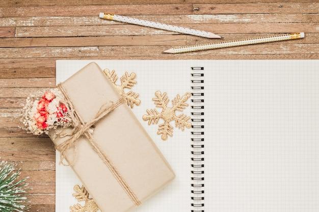 Taccuino in bianco su legno con gli ornamenti di natale e il contenitore di regalo