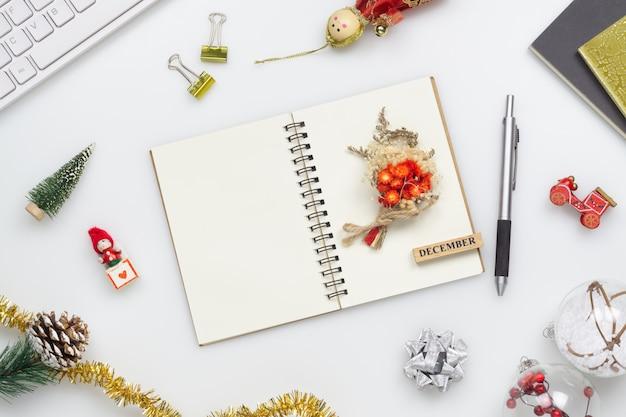 Taccuino in bianco sulla tabella bianca dell'ufficio con gli ornamenti di natale