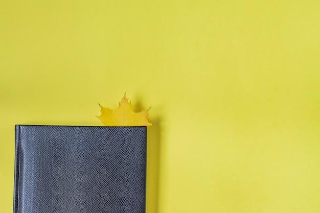 Taccuino in finta pelle di colore nero con foglia d'acero come segnalibro su giallo.