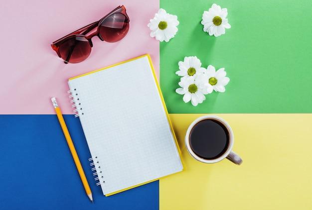 Taccuino, matita, bicchieri, caffè e fiori bianchi profumati.