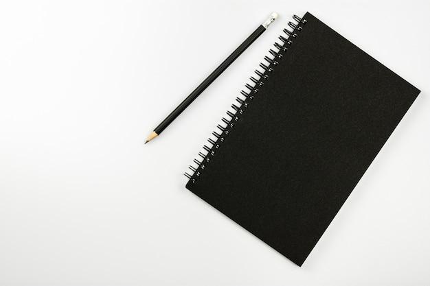 Taccuino nero e una matita sul fondo bianco dello scrittorio con lo spazio della copia