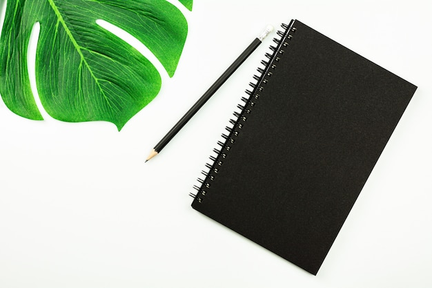 Taccuino nero e una matita sullo scrittorio bianco con lo spazio della copia. - vista dall'alto.