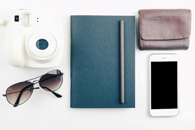 Taccuino nero, occhiali da sole, portafoglio e macchina fotografica su fondo bianco con filtro vintage. vista dall'alto.