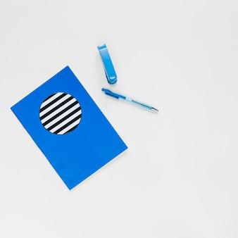 Taccuino; penna e spillatrice su sfondo bianco