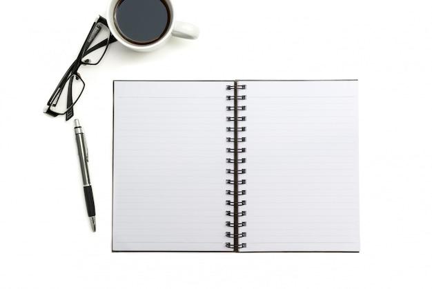 Taccuino, penna e vetri in bianco di vista superiore sul fondo bianco dello scrittorio