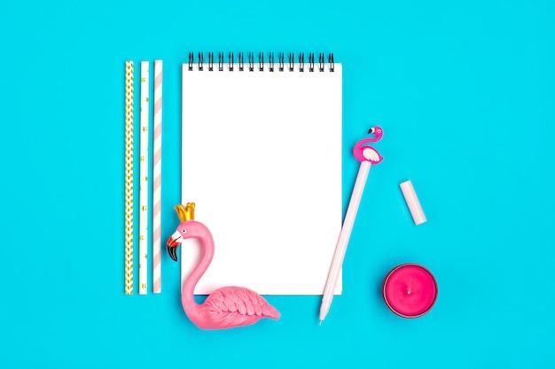 Taccuino, penna, fenicottero, smartphone, candela, cannucce di carta su sfondo blu
