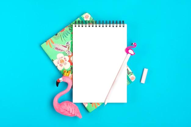 Taccuino, penna, figura di fenicottero, cannucce di carta su sfondo blu