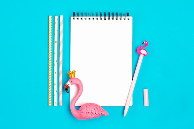 Taccuino, penna, figura di fenicottero, smartphone, cannucce di carta per bere su sfondo blu