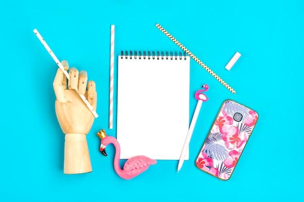Taccuino, penna, figura di fenicottero, smartphone, mano di legno tenere cannucce di carta su sfondo blu