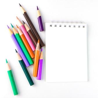 Taccuino per le note e matite su fondo bianco