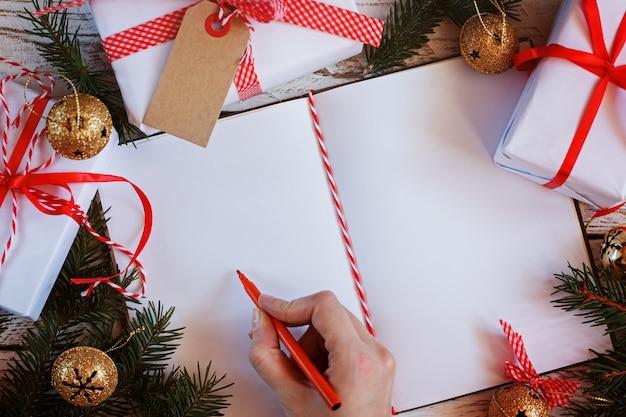 Taccuino per messaggio festivo con messaggio, confezione regalo e jingle bell dorato. natale. vista dall'alto