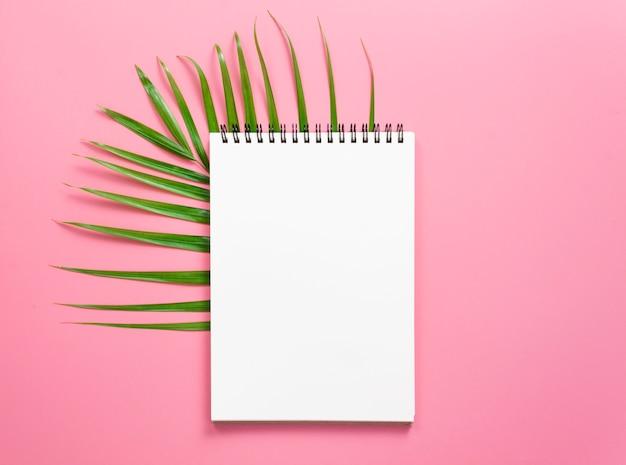 Taccuino per mock up con foglie verdi di palma su sfondo rosa brillante