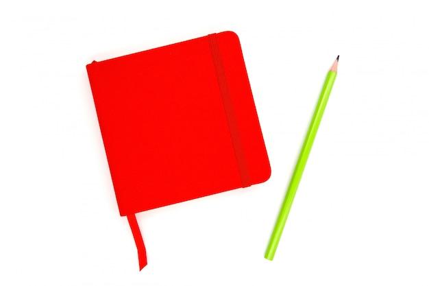 Taccuino rosso con una matita verde