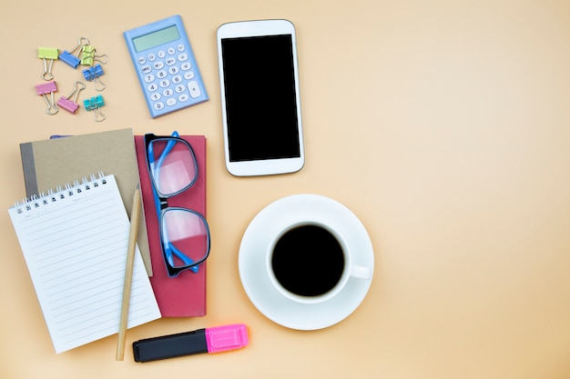 Taccuino rosso del telefono cellulare della copertura del taccuino e vetri blu della tazza bianca del caffè nero