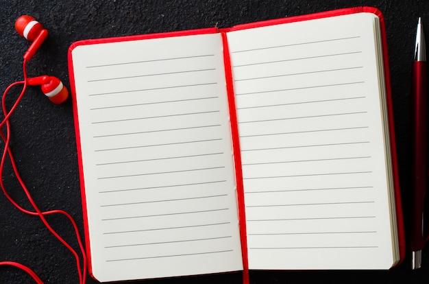 Taccuino rosso vuoto con la penna e le cuffie rosse su fondo scuro. carta bianca per il testo.