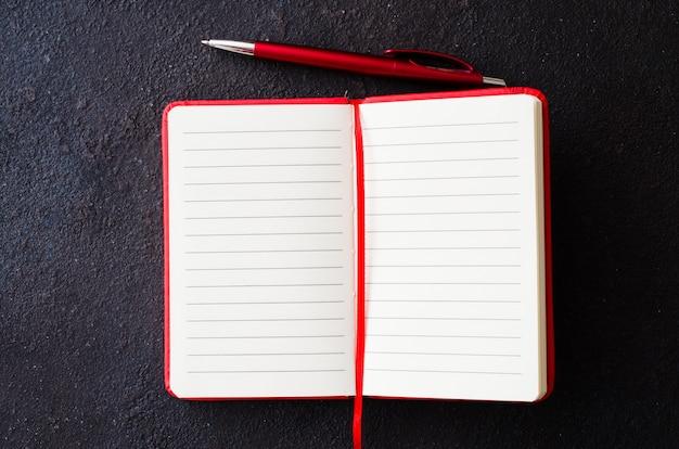 Taccuino rosso vuoto con la penna rossa su fondo scuro. carta bianca per il testo.