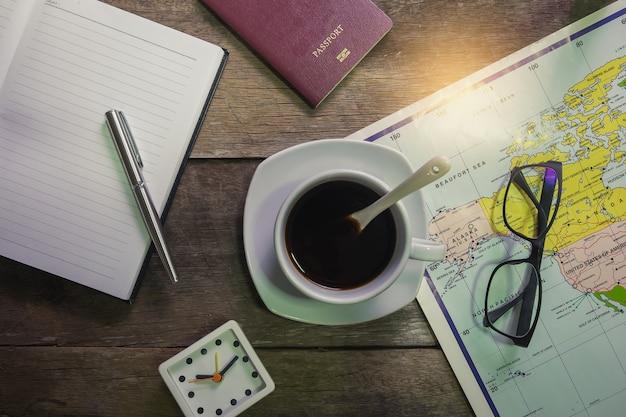 Taccuino su legno rustico con tazza di caffè e passaporto e orologio e mappa