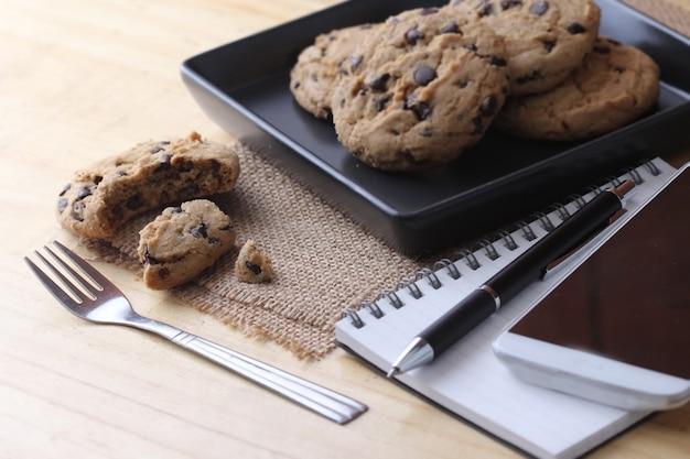 Taccuino sullo scrittorio con il biscotto e la penna del caffè