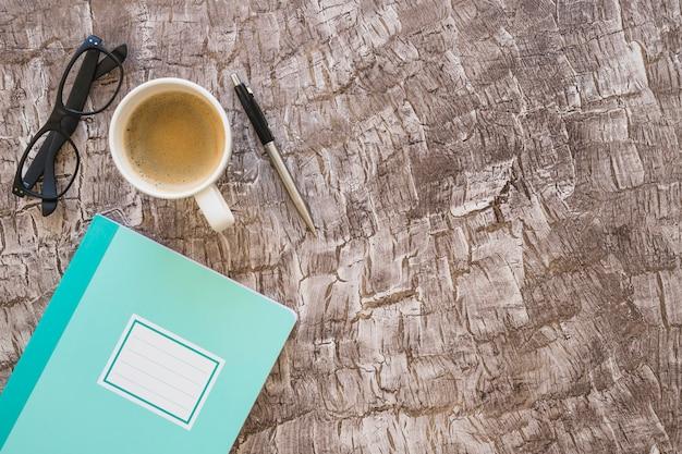 Taccuino; tazza di caffè; occhiali e penna sullo sfondo texture