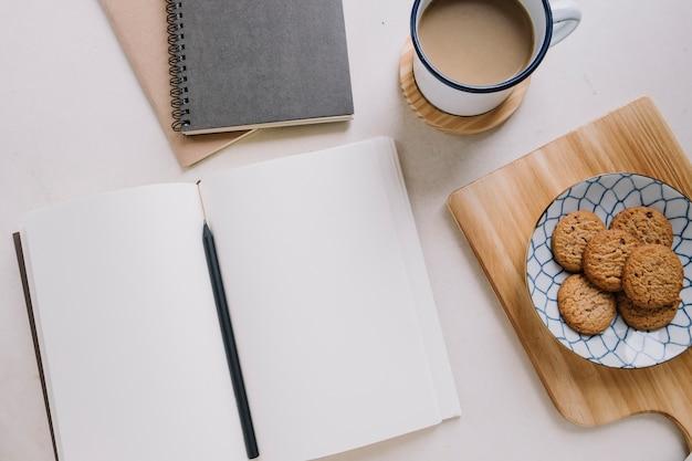 Taccuino vicino a caffè e biscotti