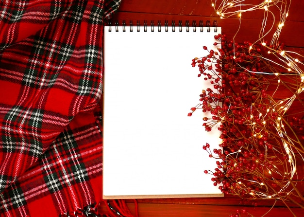 Taccuino vuoto bianco, rami con bacche rosse, sciarpa a scacchi rossa e ghirlanda splendente