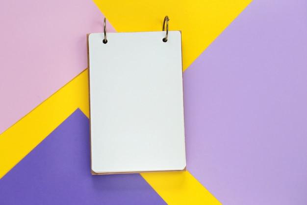 Taccuino vuoto su uno sfondo multicolore geometrico grafico. blocco note aperto vuoto su uno sfondo giallo lilla alla moda. vista piana, vista dall'alto, copia spazio